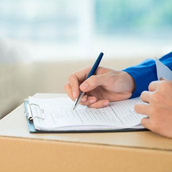 Entrümpelungsangebot Erstellung. Hand mit Stift über Angebotsblatt